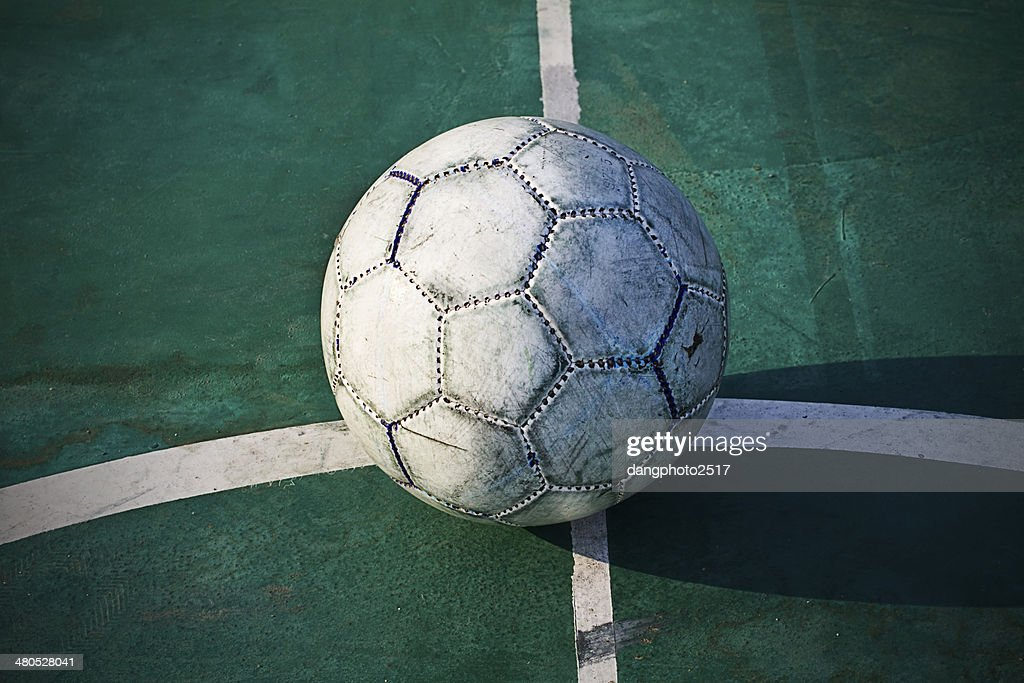 Old used football or soccer ball on cracked asphalt : Stock Photo