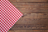 Old vintage wooden table with a red checkered tablecloth. Top view mock up.