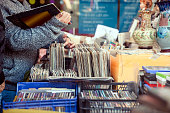 Customer browsing vybyl discs at a vintage flea market.