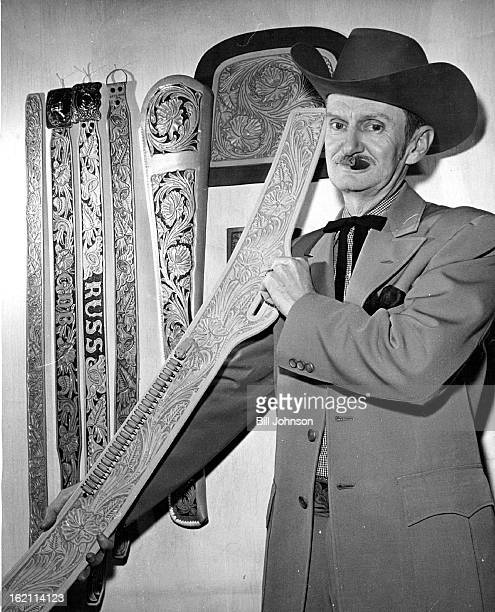 DEC 1962 DEC 12 1962 Old Western Craft Milton D Rust holds an unfinished leather gun holster In background are belts scabbard and a lady's handbag...