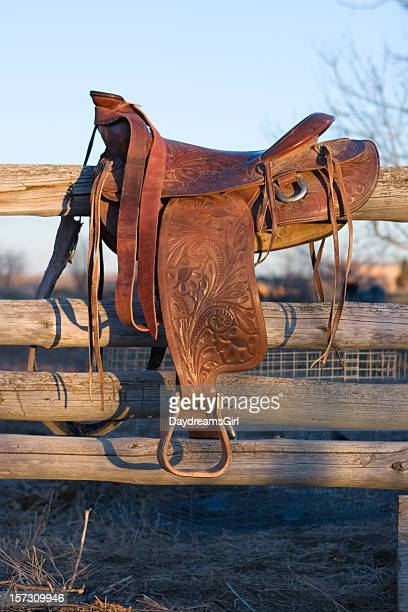 Old Western Saddle Hanging on Rustic Wood Pole Fence