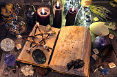 Occult, esoteric, divination and wicca concept. Halloween background with vintage objects. No foreign text, all symbols on pages are fantasy, imaginary ones