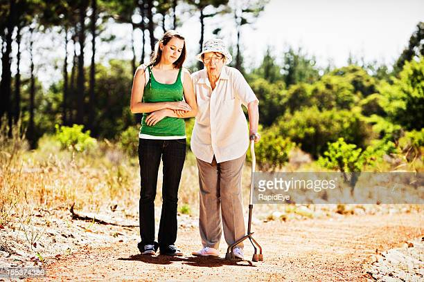 Old woman and young girl look serious on forest walk