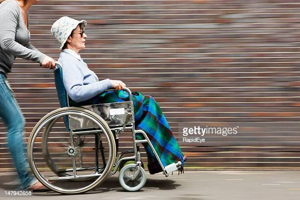 Old woman being pushed in wheelchair with motion blur