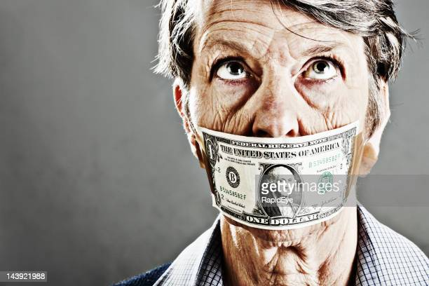 Old woman gagged with US dollar bill rolls her eyes