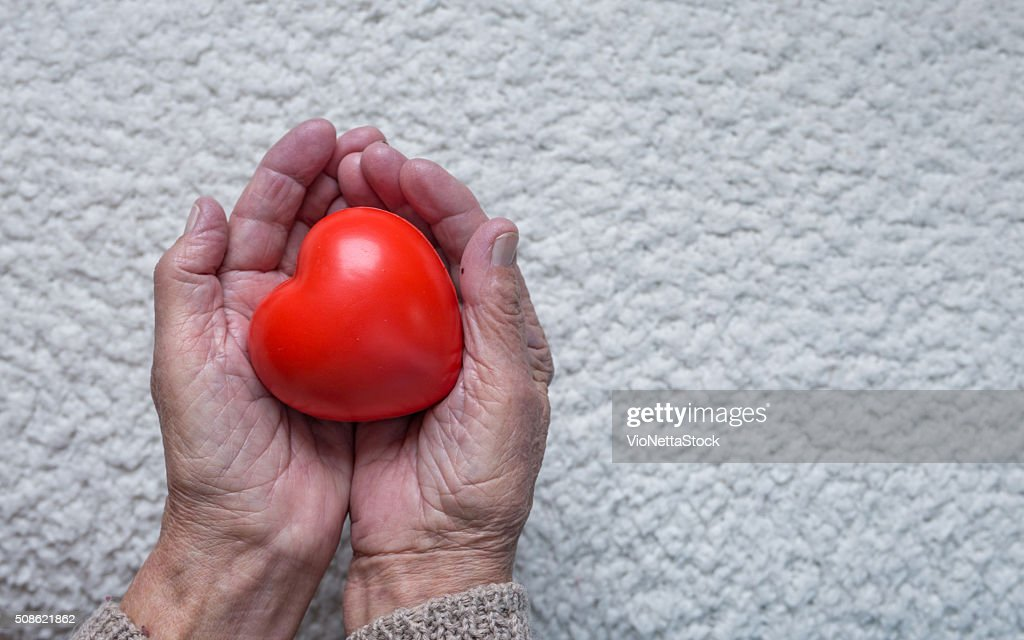 Old woman hands holding red heart, top view : Stock Photo