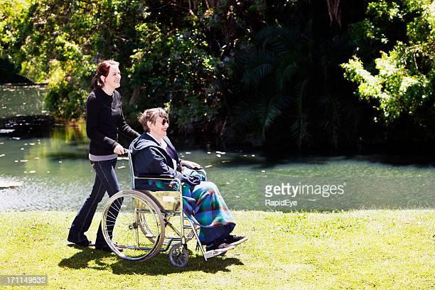 Alte Frau im Rollstuhl und junge fürsorgliche neben dem lake