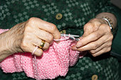 Old woman Knitting pink wool at home. Lifestyle concept