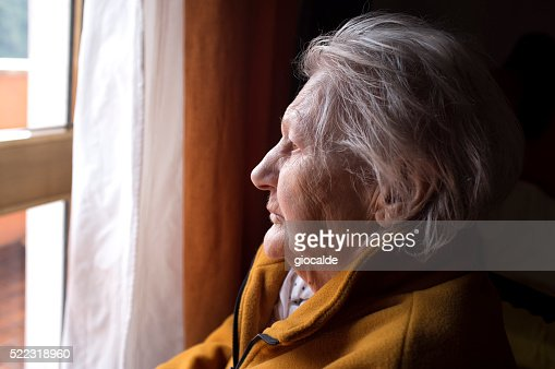 old woman looking in a window : Stock Photo