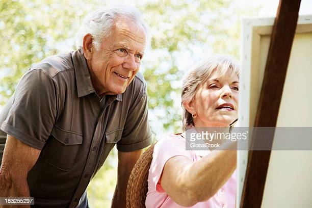 Old woman painting a picture with her husband