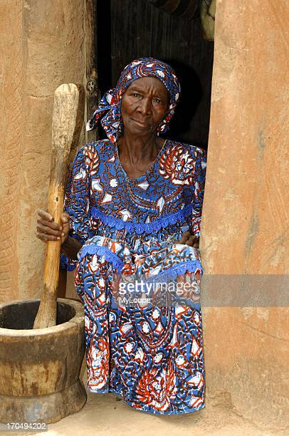 Old woman pounding maize village near Ouagadougou Burkina Faso