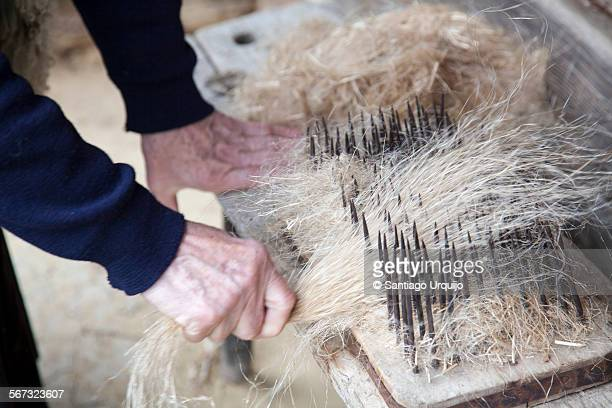 Old woman pulling flax through a comb