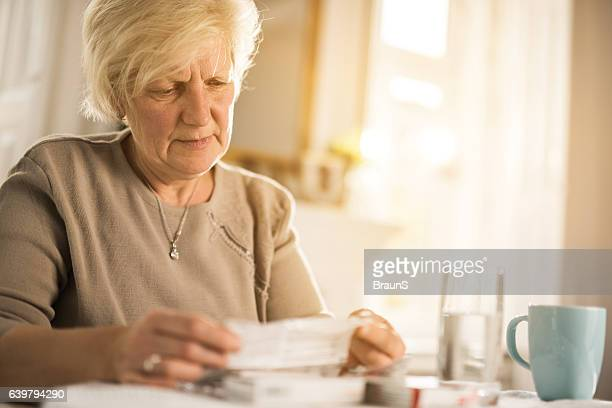 Old woman reading instructions for a medicine.