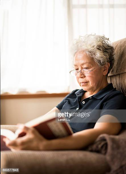 Old woman reading on sofa