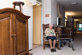 97 years old woman suffers move into retirement home while sitting on her chair in hallway; furniture stands around her