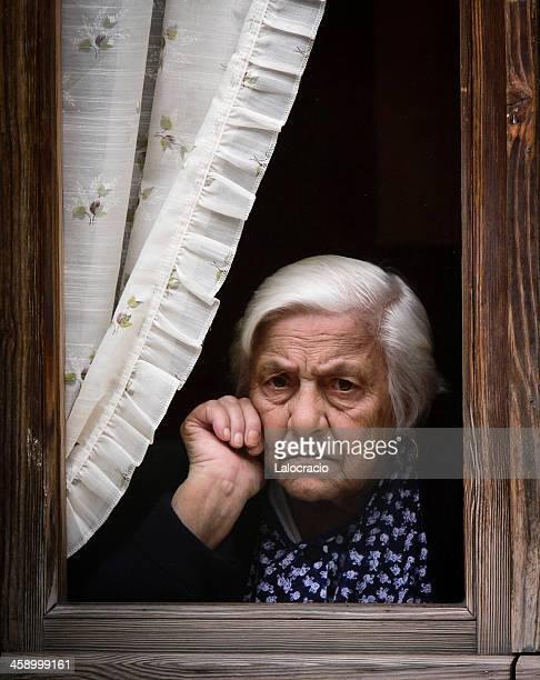 Vecchia donna attraverso la finestra.