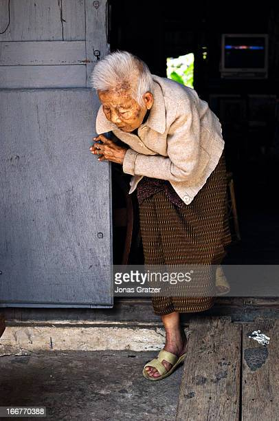 Old woman walking out of her house