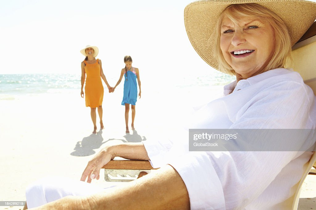 Old woman with daughter and granddaughter walking on shore : Stock Photo