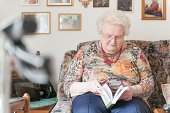 Old woman with puzzle book on couch