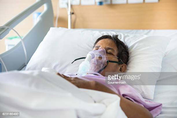 Old woman with Ventilator mask on Hospital bed