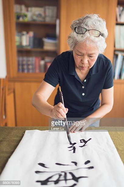 Old woman writing Chinese calligraphy