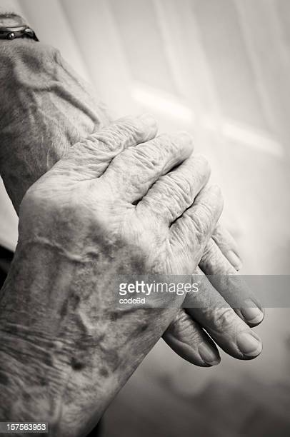Old woman's hands, folded, retirement home window, sepia toned