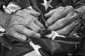 Old woman's hands holding an American flag. Black and white image. Selective focus.