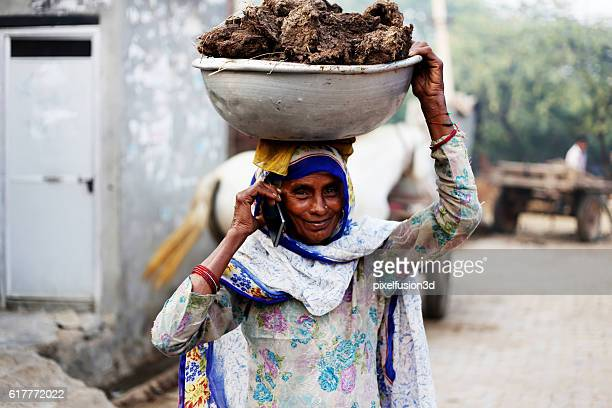 Old women carrying cow dung and talking on phone