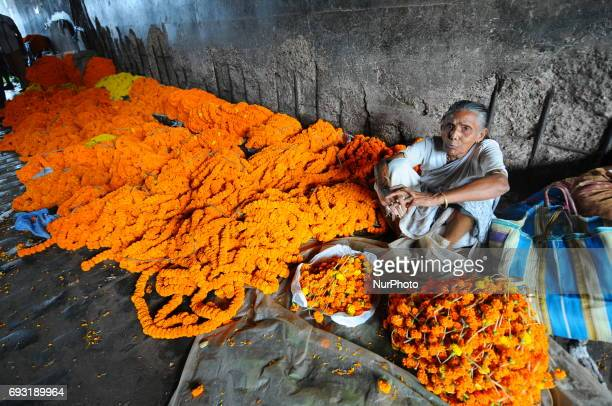 A old Women Flower Vendor waiting for Customer at the Asia Biggest Flower Market on June 072017 in KolkataIndiaWholesellers arrive at daybreak with...
