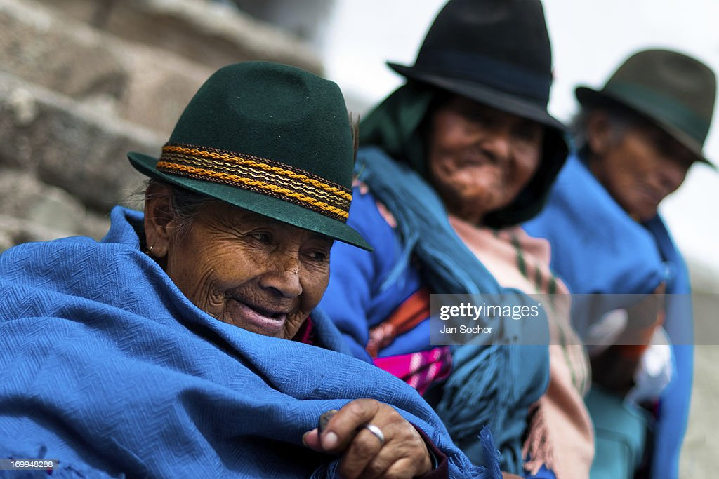 "Old women, wearing blue ponchos, watch a procession during the Inti Raymi celebration on June 26, 2010 in the village of Pesillo, Ecuador. Inti Raymi, ""Festival of the Sun"" in Quechua language, is an ancient spiritual ceremony held in the Indian regions of the Andes, mainly in Ecuador and Peru. The lively celebration, set by the winter solstice, goes on for various days. The highland Indians, wearing beautiful costumes, dance, drink and sing with no rest. Colorful processions in honor of the God Inti (Sun) pass through the mountain villages giving thanks for the harvest and expressing their deep relation to the Mother Earth (Pachamama)."