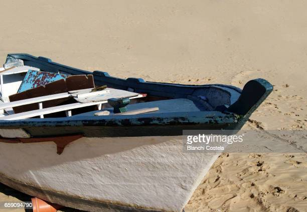 Old wooden boat on the sand of the beach