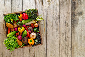 Various types of market fresh sald vegetables packed in an old wooden crate on an old wooden table. Salad vegetables includ types of lettuce, onion, tomato, cucumber, various colour capsicum, potato,