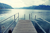 Old wooden pier with railing in rainy day on Lake Geneva, Montreux, Switzerland. Toned image