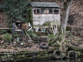old wooden run down shed or shack surrounded by garbage objects and discarded tyres at the side of a river with trees and leaves