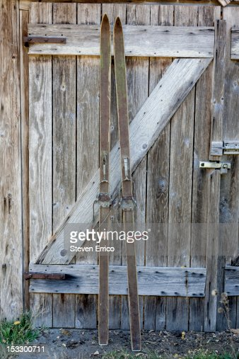 Old wooden skis leaning against a shed : Stock Photo