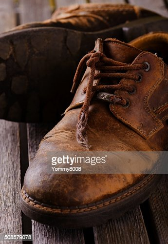 Old worn laces on brown leather boots : Stock Photo