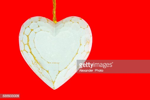 Old worn white wooden heart isolated on red background : Stock Photo