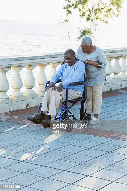 Ältere afroamerikanische Mann im Rollstuhl mit Der Fürsorgliche