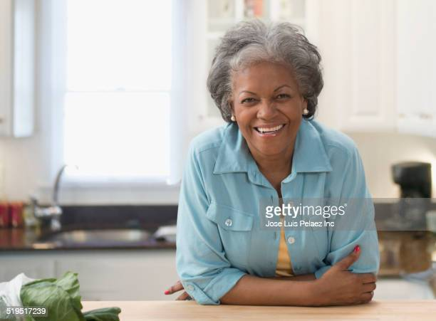 Older African American woman smiling in kitchen