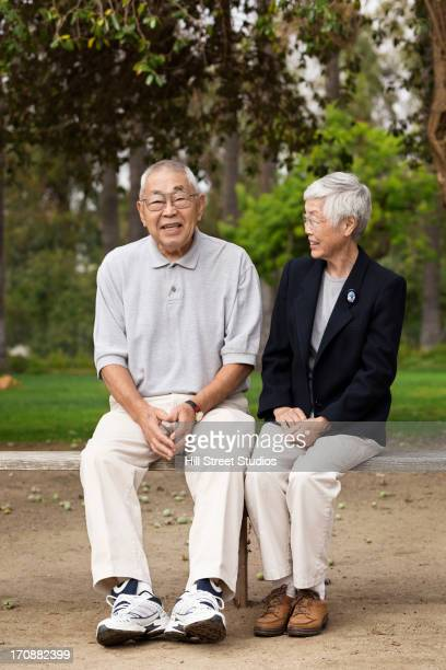 Older Asian couple smiling together outdoors