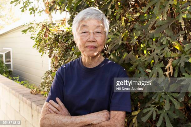 Older Asian woman standing in garden