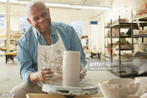 Older black man forming pottery on wheel in studio