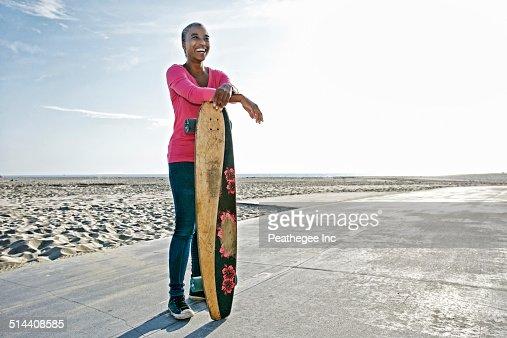 Older Black woman holding skateboard on beach