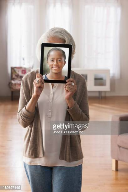 Older Black woman holding tablet computer over face