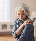 Older Black woman rubbing her shoulder