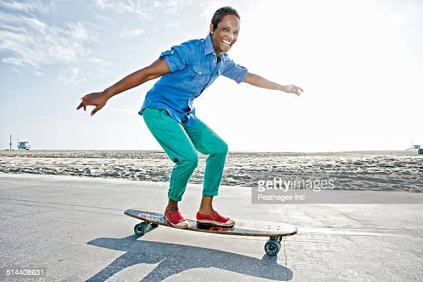 Older Black woman skateboarding by beach