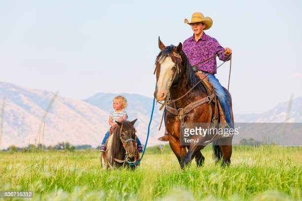 Older Brother Leads His Little Sister on Her Shetland Pony While on His Horse