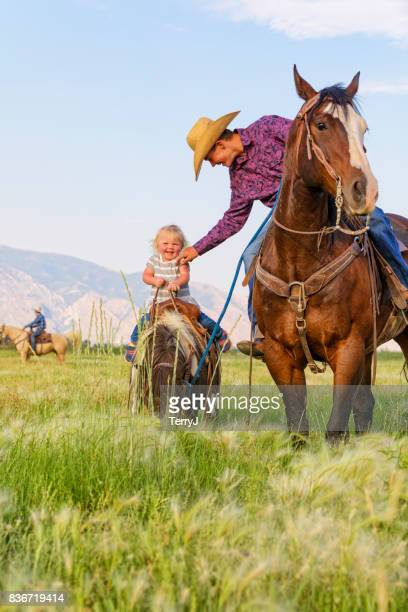 Older Brother Leans Over to Tickle His Little Sister on Her Shetland Pony While on His Horse