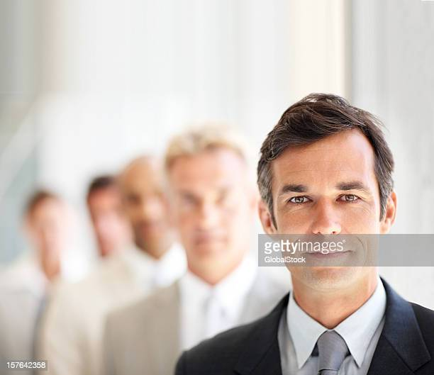 Older businessman with coworkers in line