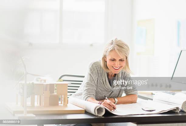 Older Caucasian architect writing on blueprints in office